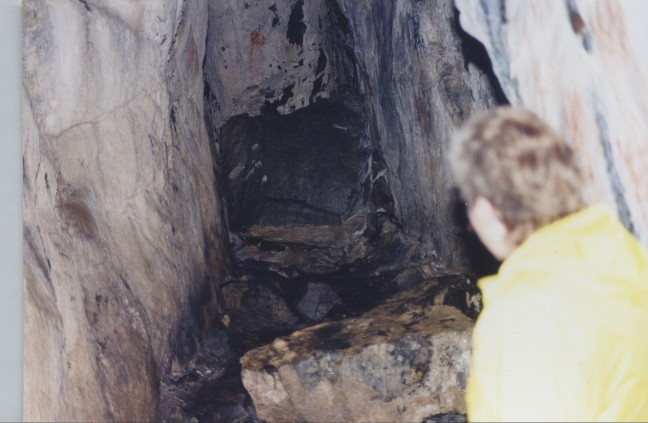 A photo of the entrance to Drynahellaren taken in the 1990s with one of Margit's relatives looking inside. Drynahellaren was renamed Franskhellaren (The French Cave) after World War II and a monument was erected close to the entrance. The story of the four escaped French POWs is told in three languages and their names are included along with their places of origin.